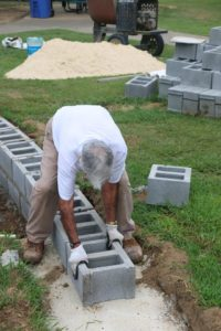 Veteran Gerald Dukes braved the heat to help lay some 12 inch blocks. (Photo by Kayron Duffey)
